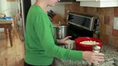 popping : a woman makes popcorn on a gas stovetop in the kitchen Stock Footage