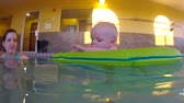 nemluvně : an underwater shot of a baby in a flotation device with his family in a swimming pool.