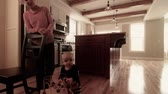 madeira de lei : baby boy standing with toy in kitchen Stock Footage