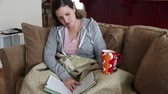 almofadas : a woman sits on a couch in her home and reads a book while drinking hot chocolate Stock Footage
