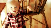 nemluvně : a baby boy standing by his high chair in the kitchen