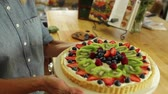 dortík : woman making a delicious fruit tart with blueberries, raspberries, strawberries, and kiwi.