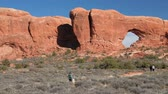 sal : Hikers walking by the north window arch in arches national park