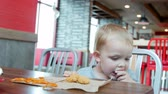 batatas fritas : A young mother with her toddler son eating a lunch at a clean and modern fast food restaurant Stock Footage