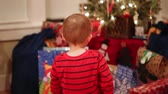 bebês : a little boy looking at his christmas presents under the tree Stock Footage
