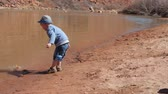 4k : A little boy plays in a sandy beach on the bank of the Green River near Moab utah Stock Footage