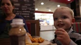 batatas fritas : a pregnant mother and her toddler eating at a fast food restaurant