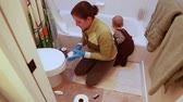 egészségügyi : a woman scrubs a toilet as she cleans the bathroom Stock mozgókép