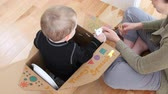 imaginar : A stay at home mother makes a spaceship from a card board box and colors it with her toddler boy