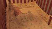 kartáček na zuby : Mother putting her baby boy to bed in his crib