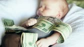 nem emberek : A baby lying in a pile of cash. Babies are expensive