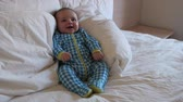 sheets : A newborn baby boy lying in a hotel bed while his family packs their suitcases and gets ready to leave for home