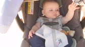 parent : An adorable newborn baby boy sleeping in his car seat while traveling