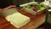 фета : preparing a delicious greek salad with feta cheese