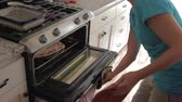ana : putting a pizza in oven