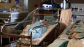entregar : a woman sleeps in a hospital bed next to her newborn son after giving birth to him