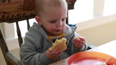 масло : a little boy eating a grilled cheese sandwich for lunch in his home