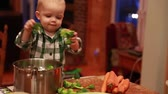 brócolis : a toddler helps his mother cook dinner while  in the kitchen