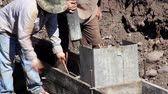 sağlam : Construction workers prepare and pour the footings of a house.