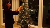 сосна : a woman decorates a small christmas tree in a house
