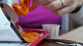batatas fritas : Woman eating curly fries at a fast food restaurant