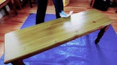 furniture : woman staining a wooden bench
