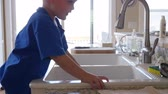 não higiênico : A little boy playing in the kitchen sink with the water