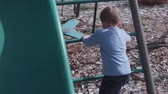 file : A little boy playing on a fun swingset Stok Video