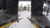 осина : A low shot skis on ski lift on cold day
