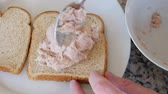 konserve : A man puts tuna fish on bread for a sandwich Stok Video
