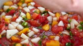 peeling onion : A man stirs colorful peach salsa in kitchen