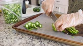 peeling onion : A woman cutting jalapenos for salsa in her kitchen Stock Footage