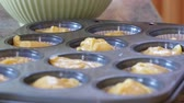 jedzenie : A woman makes cupcakes in kitchen