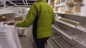 inexpensive : A woman walking through ikea to look at furniture