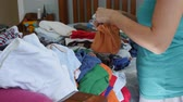 housekeeping : A young mother sorts through the kids clothes