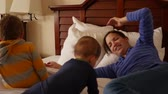 upscale : An interior dolly shot of cute family on hotel room bed Stock Footage