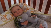 bebês : Cute baby boy with his big eyes in his crib in the room dolly shot