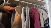 szafy : Dolly shot of a man picking out a shirt in his closet Wideo