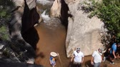 à beira da piscina : Family hiking a waterfall running through slot canyon in desert
