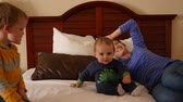 upscale : Interior dolly shot of a family on hotel room bed