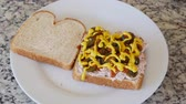 przetwory : Man puts mustard on tuna fish sandwich