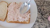 conservado : Man puts tuna fish on bread for a sandwich