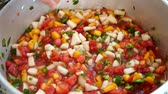 peeling onion : Man stirs colorful peach salsa in kitchen