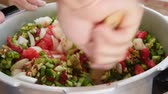 peeling onion : Man stirs chopped vegetables for salsa in kitchen Stock Footage