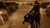 entrada da garagem : Mother and toddler push baby in stroller through parking garage Vídeos