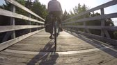 фитнес : Woman on bike rides over tall wooden bridge