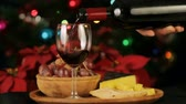 красное вино : Serving Wine Christmas Theme Slow Mo (HD). Wine glass being served with a Christmas tree and poinsettia flowers out of focus in the background. Very shallow depth of field shot.