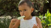 ano : Hispanic Girl Eating Ice Pop Close Up (HD). Close up shot of Lemon Ice pop being eaten by a 4 year old Hispanic girl.