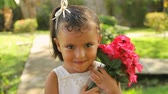 smiling girl : Girl Holding Gardenia Flowers. Hispanic girl holding pink gardenia flowers with a happy face. Stock Footage