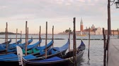 veneza : Venice Gondolas San Giorgio Maggiore (HD). Blue gondola boats docked near plaza Saint Marks Square in Venice Italy with far away view of San Giorgio Maggiore church. All logos and boat IDs removed.